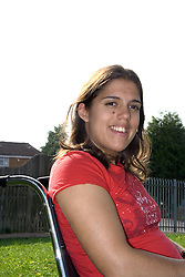 Young woman with Cerebral Palsy; sitting in a wheelchair; smiling,