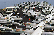 A red shirted ordnance man walks through a crowd of US Navy fighter and intelligence-gathering jets on deck of USS Harry S Truman. The Truman is the largest and newest of the US Navy's fleet of new generation carriers, a 97,000 ton floating city with a crew of 5,137, 650 are women.