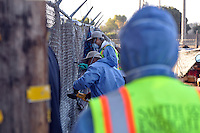 Private contractors tear down the fencing at 38 Soledad St in Salinas.