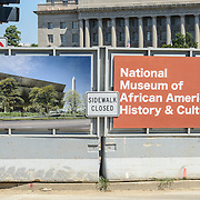 Smithsonian National Museum of African American History and Culture Construction Signs. Signs and barrier at the Smithsonian National Museum of African American History and Culture work zone. It is being constructed on the National Mall at the corner of Constitution Avenue and 15th Street NW.