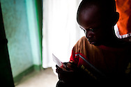 A son of Eunice Werema, widow of Mwita Werema looks at a photograph of his late father in Nayagota, Tanzania, on Wednesday, July 28, 2010. Photographer: Trevor Snapp