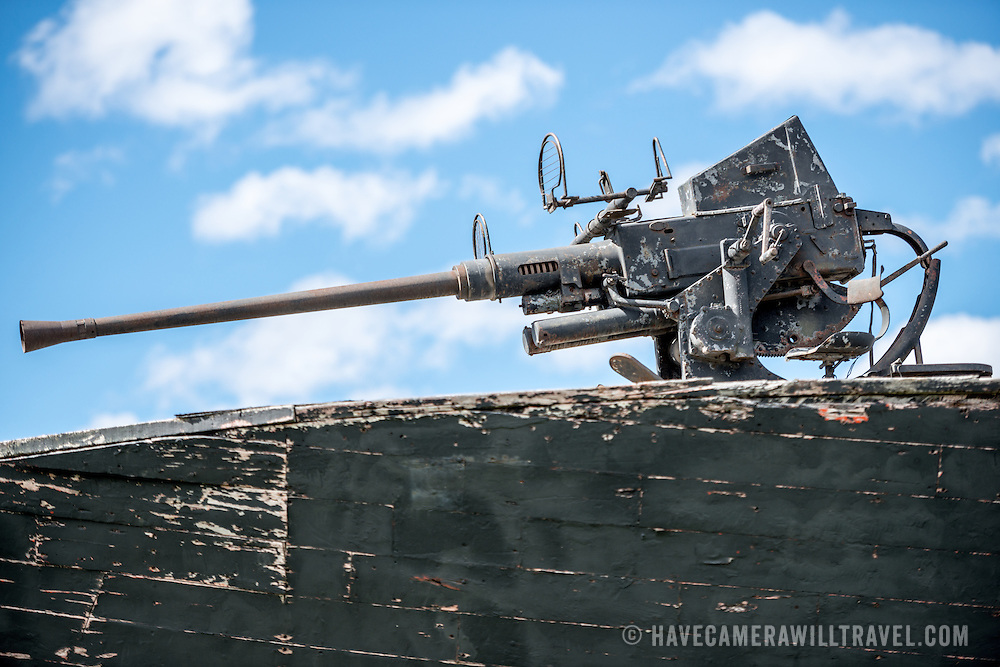 An artillery gun on the bow of a PT boat, formerly of the Argentinian Navy, the Ara Towwora, that sits on the shore of Ushuaia Harbor as a naval monument.