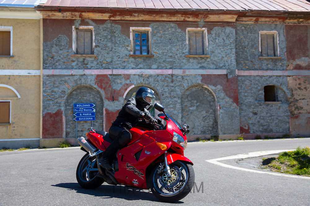 Motorcyclist on Honda VFR drives The Stelvio Pass, Passo dello Stelvio, Stilfser Joch, to Bormio, Northern Italy