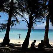 A beach scene by the pristine waters at White Beach on October 4, 2008 in Boracay Island, the Philippines. Photo Tim Clayton..Asian tourists at White Beach, Boracay Island, the Philippines...The 4 km stretch of White beach on Boracay Island, the Philippines has been honoured as the best leisure destination in Asia beating popular destinations such as Bali in Indonesia and Sanya in China in a recent survey conducted by an International Travel Magazine with 2.2 million viewers taking part in the online poll...Last year, close to 600,000 visitors visited Boracay with South Korea providing 128,909 visitors followed by Japan, 35,294, USA, 13,362 and China 12,720...A popular destination for South Korean divers and honeymooners, Boracay is now attracting crowds of tourists from mainland China who are arriving in ever increasing numbers. In Asia, China has already overtaken Japan to become the largest source of outland travelers...Boracay's main attraction is 4 km of pristine powder fine white sand and the crystal clear azure water making it a popular destination for Scuba diving with nearly 20 dive centers along White beach. The stretch of shady palm trees separate the beach from the line of hotels, restaurants, bars and cafes. It's pulsating nightlife with the friendly locals make it increasingly popular with the asian tourists...The Boracay sailing boats provide endless tourist entertainment, particularly during the amazing sunsets when the silhouetted sails provide picture postcard scenes along the shoreline...Boracay Island is situated an hours flight from Manila and it's close proximity to South Korea, China, Taiwan and Japan means it is a growing destination for Asian tourists... By 2010, the island of Boracay expects to have 1,000,000 visitors.
