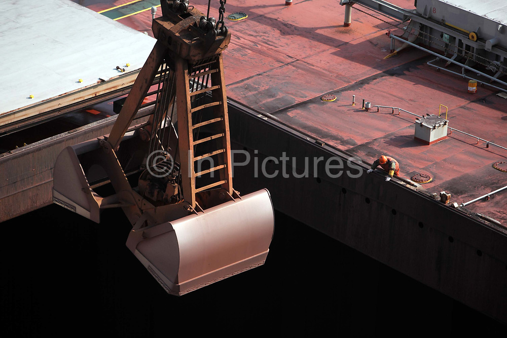A mechanical scoop unloads a bulk carrier cargo ship docked at an iron-ore transfer and storage center operated by the Shanghai International Port Group in Shanghai, China on 26 January 2010. China's economic boom and hunger for natural resources has been a blessing for countries such as Australia and Brazil, who controls most the world's high quality iron ore deposits.