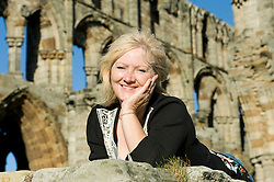 Attractive blonde older woman poses for photo at whitby abbey