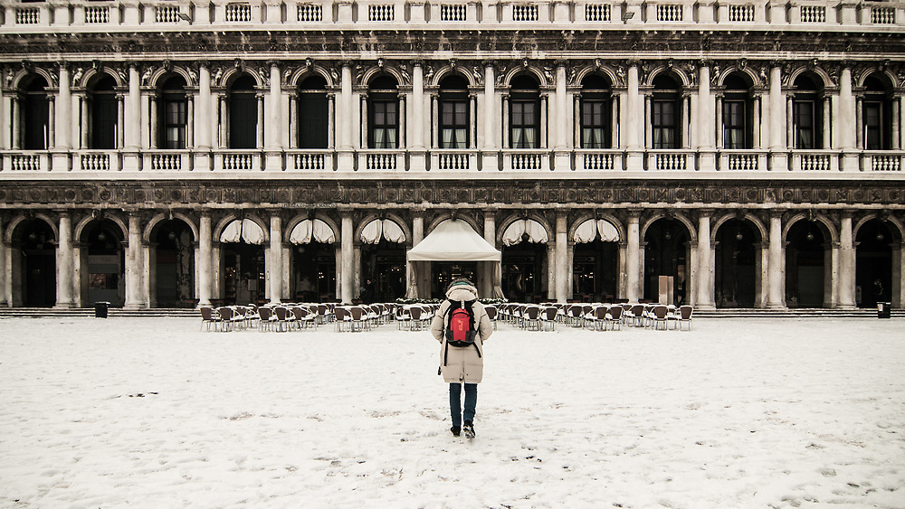"""VENICE, ITALY - 28th FEBRUARY/01st MARCH 2018<br /> A woman looks at Procuratie Nuove in Saint Mark square during a snowfall in Venice, Italy. A blast of freezing weather called the """"Beast from the East"""" has gripped most of Europe in the middle of winter of 2018, and in Venice A snowfall has covered the city with white, making it fascinating and poetic for citizen and tourists.   © Simone Padovani / Awakening"""