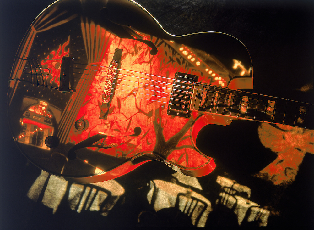 Depiction of Pat Methany's signature Ibanez guitar with a an image of a jazz club overlay. Four tables with white tablecloths, orange and gold design on face of guitar,