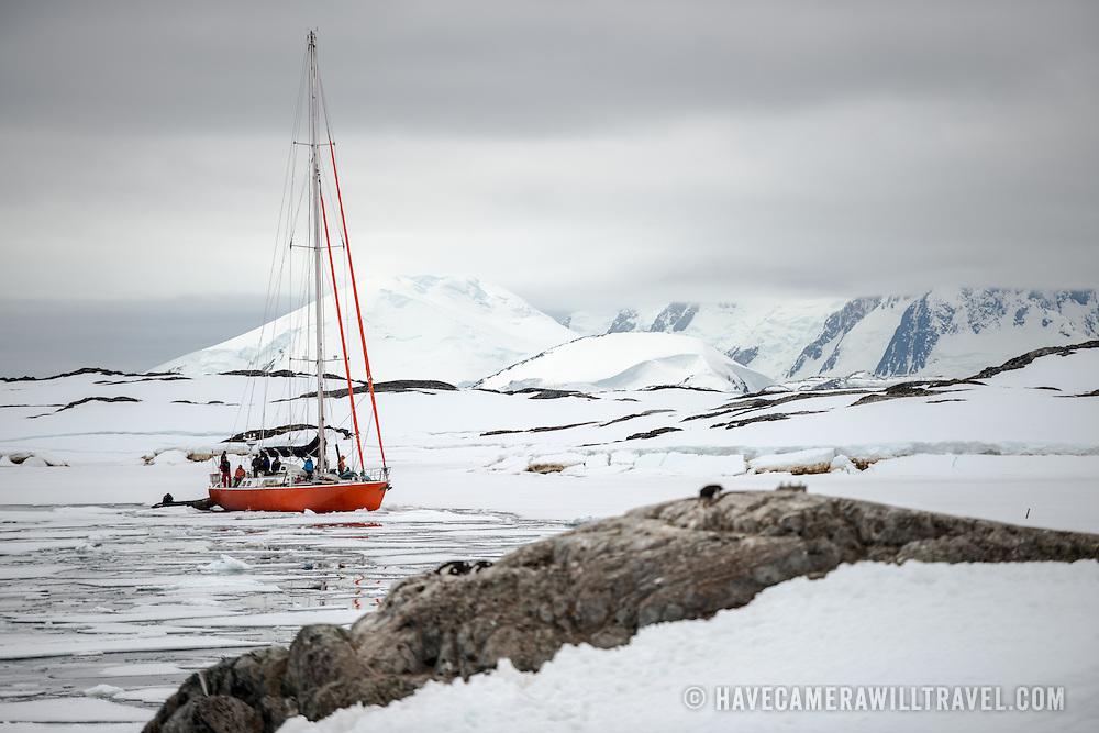 A sailboat moves carefully through the sheets of sea ice near Galindez Island on the Antarctic Peninsula.