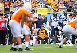 Sep 1, 2018; Charlotte, NC, USA; West Virginia Mountaineers defensive coordinator Tony Gibson squats on the sidelines during the second quarter against the Tennessee Volunteers at Bank of America Stadium. Mandatory Credit: Ben Queen-USA TODAY Sports