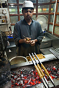 A man makes and griddles kebabs at Karims Restaurant, Old Delhi