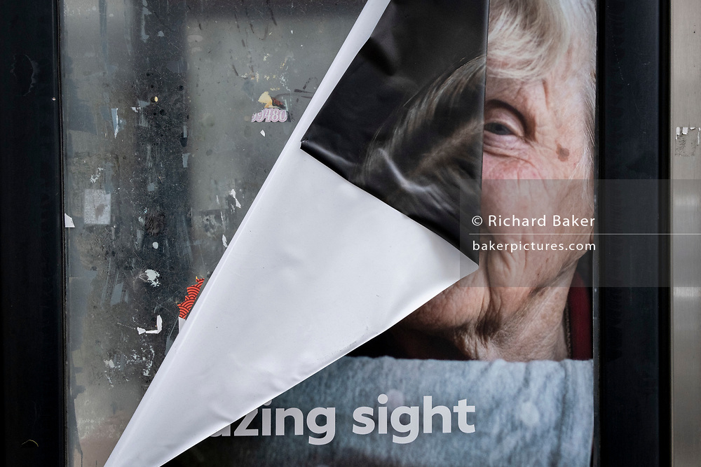 Days before the third Coronavirus lockdown ends, and non-essential retailers and shops re-open again, the torn poster of a Specsavers opticians ad, obscures the face of an elderly woman, pasted to the window of a phone kiosk on Oxford Street,  on 9th April 2021, in London, England.