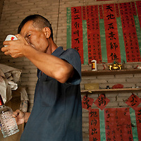 Wei Xinyuan takes a bowl of Chinese hard alcohol in the afternoon. The spirits help him with his aches, and make the day go a little smoother. Once he was the local schoolteacher, a position of prominence in the village, but after his car accident he had to give up the position. Now most of his days are spent watching over his precious water buffalo.
