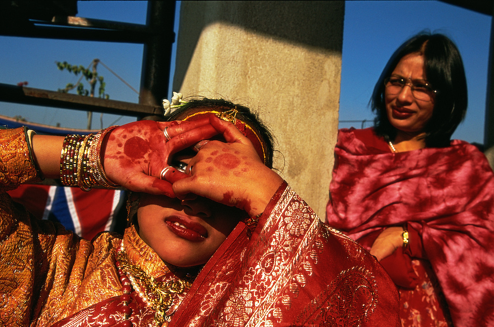 A young Newar girl, who has been secluded in a room at home for twelve days during her barha ceremony, is taken to the roof of the family house to show herself to the sun god Surya, Kathmandu, Nepal. The barha is a Newar mock first-menstruation rite, held before the girl's first menstruation. During the seclusion, no male above the age of initiation is allowed to see the girl, and the windows of the room are covered so that the rays of the sun god, who is a male, cannot shine on her. The ceremony is also a mock-marriage, as it is said that the girl is married to Surya when she shows herself to him after the seclusion. The mother is standing behind the girl.
