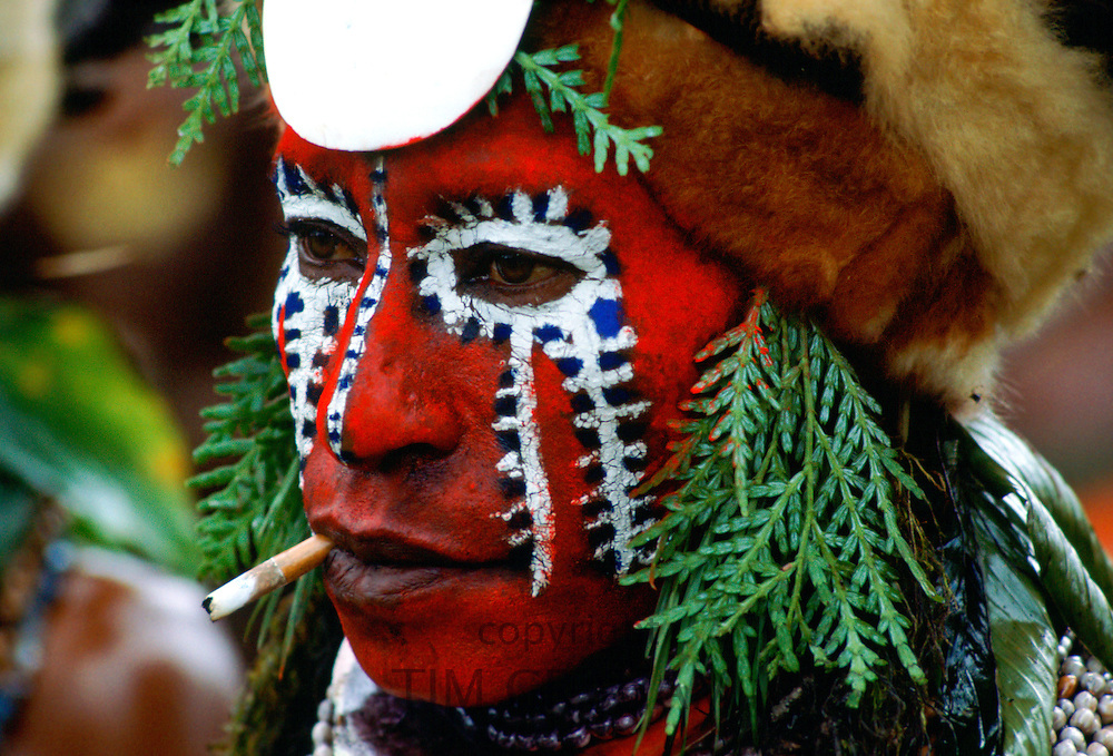 Tribesman with painted face and a cigarette at a tribal gathering in Papua New Guinea