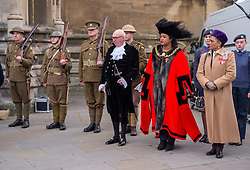 "© Licensed to London News Pictures. 27/10/2018. Bristol, UK. The Royal British Legion launch this year's Bristol Poppy Appeal, ""One thousand poppies, for one hundred years, for one million lives"" at Bristol Cathedral. For the launch of the 2018 Bristol Poppy Appeal at 11am on 27 October, the Royal British Legion recreated a scene from the end of WW1 outside Bristol Cathedral on College Green, and Colonel Clive Fletcher-Wood read the war poem In Flanders Fields. They were joined by Civic Dignitaries pictured left-right, City of Bristol High Sheriff Mr ROGER OPIE, Bristol's Lord Mayor CLEO LAKE and the Lord Lieutenant of Bristol PEACHES GOLDING. A Bugler and the Bristol Military Wives Choir performed songs from their new album 'Remember'. Staff at MOD Filton filled 400 sandbags with eight tonnes of sand to build trenches and recreate 'Flanders Fields' and planted over 1000 waterproof poppies on College Green. Poppies and sandbags can be sponsored by individuals wanting to remember those who fought and died in conflict. There were re-enactors in WW1 uniform from Somerset Light Infantry (known as the West Country Tommys), as well as medics and nurses with equipment from the time. Bristol's own 'War Horse' (Buzz from Blagdon Horsedrawn Carriages) was on College Green behind the improvised barbed wire to represent the 350,000 horses that left Avonmouth for the frontline during WW1. There are also 10,000 knitted poppies on display both in and outside Bristol Cathedral following 'The Charfield Yarn Bombers' incitement to locals to get knitting to mark the occasion, with a display inside the Cathedral organised by Helen Date. Photo credit: Simon Chapman/LNP"