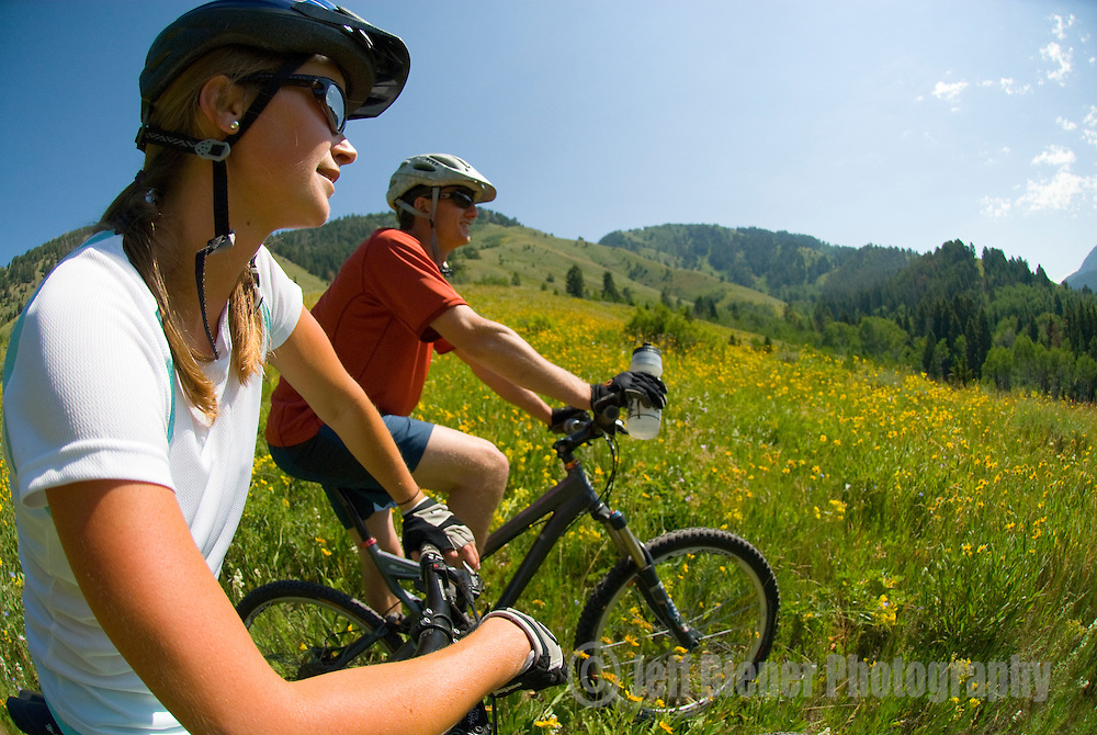 A young couple rests while mountain biking in the Cache Creek area near Jackson, Wyoming.