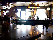 a person playing billiard in a Belgium bar on a sunny Sunday afternoon
