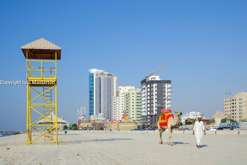 Man with camel walking on beach on waterfront of Ajman emirate in United Arab Emirates