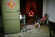A woman and her daughter watch television  in front of a Buddhist altar in an old neighborhood in the Chinese town of Jingdezhen in the southern province of Jiangxi. The town's back alleys and urban neighborhoods come alive as soon as the sun sets and the sweltering summer temperatures dip slightly.