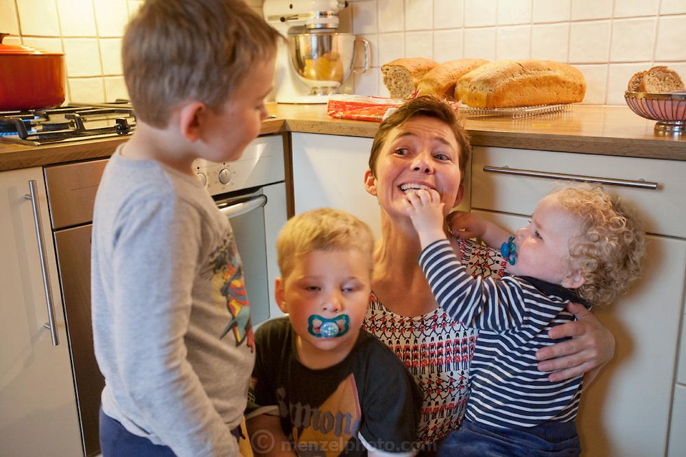 Ottersland Dahl family, of Gjettum, Norway (outside Oslo). In the kitchen after baking bread. Gunhild Valle Ottersland, 45, and their three children, Olav, 6 Hakon, 3, and Sverre, 1.5 Model-Released.