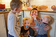 Ottersland Dahl family, of Gjettum, Norway (outside Oslo). In the kitchen after baking bread. Gunhild Valle Ottersland, 45, and their three children, Olav, 6 Hakon, 3, and Sverre, 1.5 Model-Released.