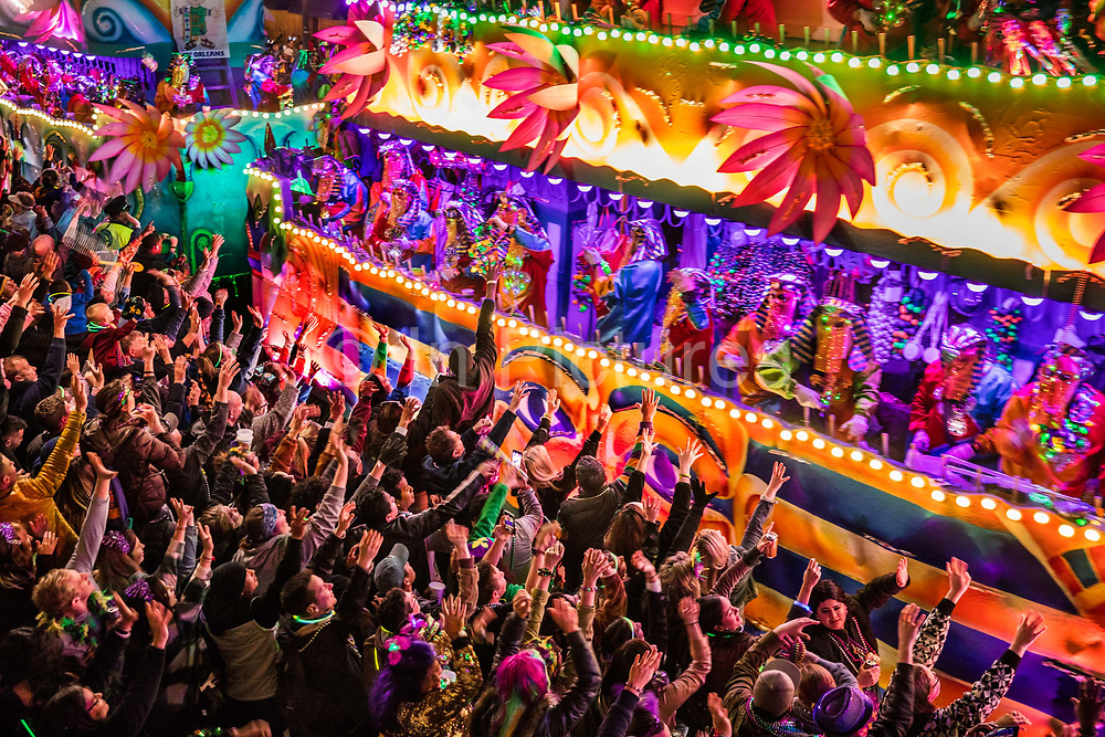 Crowds screaming for beads thrown from floats on the Endymion parade during Mardi Gras on 22nd February 2020 in New Orleans, Louisiana, United States. Mardi Gras is the biggest celebration the city of New Orleans hosts every year. The magnificent, costumed, beaded and feathered party is laced with tradition and  having a good time. Celebrations are concentrated for about two weeks before and culminate on Fat Tuesday the day before Ash Wednesday and Lent. The average Endymion rider will throw 500 pounds of beads. With a membership of roughly 3200, thats an 800-ton trove thrown to the crowd.