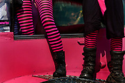 two sets of legs adorned with pink striped leggings, stand on a car. Glastonbury Festival 2010