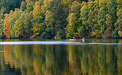 Autumn colours on trees and member of public in kayaks on Loch Faskally in Pitlochry, Scotland, UK