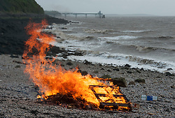 © Licensed to London News Pictures.  06/05/2015. Clevedon, North Somerset, UK.   'Figures' is burnt on the beach at Ladye (correct) Bay in Clevedon, with 650 stories from people at the sharp end of austerity read out and recorded nearby.  The art is by Liz Crow and was displayed in a mobile gallery built into a van.  On election's eve, 6 May, at lowest tide, 650 stories from people at the sharp end of austerity was read aloud in a live performance lasting six hours, which will also be audio-streamed from www.WeAreFigures.co.uk. Audiences internationally are invited to bear witness to the human cost of austerity.  The reading will be accompanied by the ceremonial firing of 650 small clay human figures, each one paired with one of the 650 stories. 650 echoes the number of constituencies throughout which austerity is felt and the number of MPs whose choices determine the choices of others. The figures will be raised into a bonfire that will burn into the night.Each figure has been hand-sculpted by artist-activist Liz Crow from raw river mud, collected by hand from the River Avon. In a feat of endurance, Liz sculpted the figures last month at low tide on the Thames foreshore over 11 consecutive days and nights and in all weathers. Each time a figure was made, its corresponding story was released on social media.  The 650 stories have been drawn from leading-edge research, Parliamentary records and campaigns in the field of social justice. Covering a range of topics, including benefits reform, local authority spending, homelessness, malnutrition, NHS rationing, etc. Photo credit : Simon Chapman/LNP