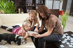 Woman with her two daughters playing games on a digital tablet in a living room, Bavaria, Germany