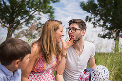 Couple eating raspberries from fingers on meadow in the countryside, Bavaria, Germany