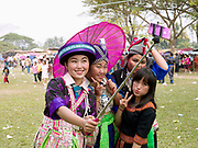 Young Hmong Der (White Hmong) women wearing contemporary Hmong traditional costumes taking selfie portraits on a mobile phone at Ban Km 52 Hmong New Year celebration Vientiane province, Lao PDR. The Hmong celebration of New Year is based on the lunar calendar. This important time is an opportunity to honour ancestors and spirits through offerings and rituals and to partake in games, sports, feasts, shows, bullfights and courtship. The Hmong are the third largest ethnic group in Laos. One of the most ethnically diverse countries in Southeast Asia, Laos has 49 officially recognised ethnic groups although there are many more self-identified and sub groups. These groups are distinguished by their own customs, beliefs and rituals.