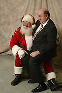 Santa Harry Winters, of Costa Mesa, lets piano player Mark Davidson sit on his lap during a private party at the Big Canyon Country Club in Newport Beach Wednesday December 3, 2003. He stops trimming his beard every May 5th to get ready for the holiday season.