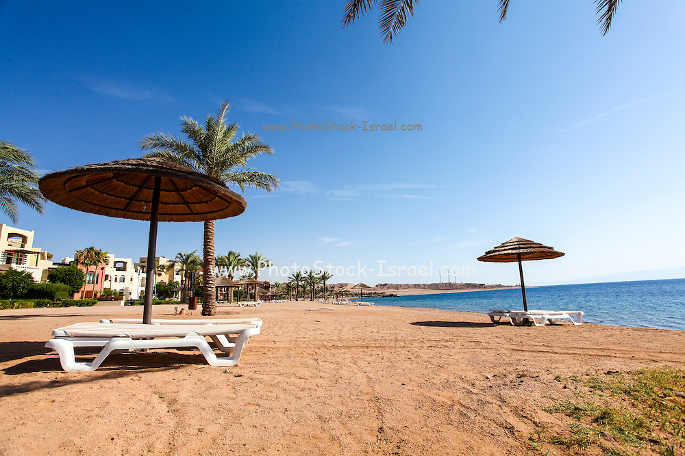 Jordan, Aqaba, Tala Bay beach with a parasol and sunning beds