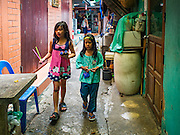 13 AUGUST 2016 - BANGKOK, THAILAND:  Girls who live in Pom Mahakan slum in Bangkok walk to their home after buying soft drinks from a small shop in the slum. Residents of the slum have been told they must leave the fort and that their community will be torn down. The community is known for fireworks, fighting cocks and bird cages. Mahakan Fort was built in 1783 during the reign of Siamese King Rama I. It was one of 14 fortresses designed to protect Bangkok from foreign invaders. Only of two are remaining, the others have been torn down. A community developed in the fort when people started building houses and moving into it during the reign of King Rama V (1868-1910). The land was expropriated by Bangkok city government in 1992, but the people living in the fort refused to move. In 2004 courts ruled against the residents and said the city could take the land. Eviction notices have been posted in the community but most residents have refused to move. Residents think Bangkok city officials will start evictions around August 15, but there has not been any official word from the city.      PHOTO BY JACK KURTZ