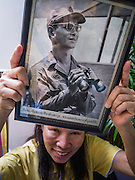 04 DECEMBER 2012 - BANGKOK, THAILAND: A woman dressed in yellow holds up a picture of Bhumibol Adulyadej, the King of Thailand, while she waits for him in the lobby of Siriraj Hospital. People pack the lobby of the hospital hoping the catch a glimpse of the King if he should make an unexpected visit to the lobby. Yellow is the official color of the Thai King, who celebrates his 85th birthday Wednesday, Dec. 5. The King lives in Siriraj. He is expected to make a rare public appearance and address the nation from Mukkhadej balcony of the Ananta Samakhom Throne Hall in the Royal Plaza. The last time he did so was in 2006. His birthday is a public holiday in Thailand and hundreds of thousands of people are expected to jam the streets around the Royal Plaza and Grand Palace to participate in the festivities.    PHOTO BY JACK KURTZ