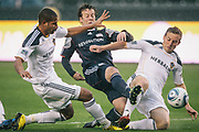 New England Revolution forward Zack Schilawski, middle, battles Los Angeles Galaxy defender Leonardo, left, and Los Angeles Galaxy midfielder Chris Birchall for the ball during the first half of an MLS soccer match, Sunday, Mar. 20, 2011, in Carson, Calif. (AP Photo/Bret Hartman)