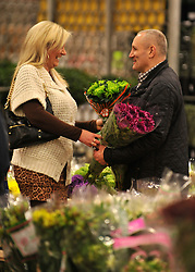 © Licensed to London News Pictures. 15/03/2012. London, UK. A woman buys flowers from a wholesaler. The Mothering Sunday sales rush is on for flower growers, suppliers, florists and retailers amongst the Flowers at the New Covent Garden Flower Market on March 15th 2012 in London, England. New Covent Garden Flower Market is London's premier wholesale market stocking the widest range of flowers, plants and foliage in the UK. The run up to Mothers' Day is crucial in the flower selling calendar as Mothers' Day sales are condensed into about four days making the market very busy. Traditionally, Mothering Sunday was a day when children, mainly daughters, who had gone to work as domestic servants, were given a day off to visit their mother and family. Today, Mother's Day is a time when children give flowers and cards to their mothers, and generally pamper them..  Photo credit : Stephen SImpson/LNP