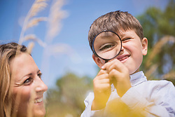 Little boy looking through magnifying glass with his mother in the countryside, Bavaria, Germany