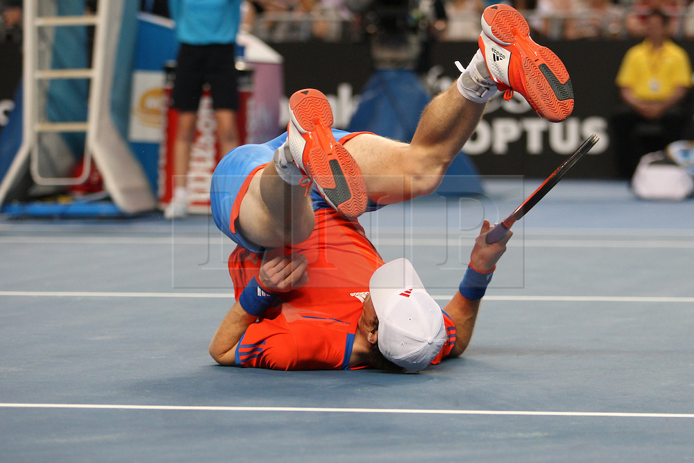 © Licensed to London News Pictures. 21/01/2012. Melbourne Park, Australia. Andy Murray (GBR) rolls over after losing his balance in his men's singles match against Michael Llodra (FRA) during the 6th day, round 3 of the Australian Open. Photo credit : Asanka Brendon Ratnayake/LNP