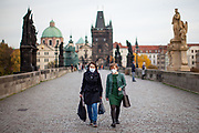 Two woman wearing face masks  while passing Charles Bridge in Prague. As of 21st of October 2020 people have to wear face masks outside and inside.