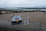 The morning after Saturday night crowds of young peoples' nightlife beach parties, their litter and rubbish from the night before stretches across the coastal paths and shingle, a box of Corona beers and a Vodka bottle is on the sea wall, on 19th July 2020, in Whitstable, Kent, England.  A group of local volunteers and council cleaner will soon arrive for the regular morning clean-up that has got worse, they say, during the Coronavirus pandemic lockdown and now, the slow easing of health guidelines.