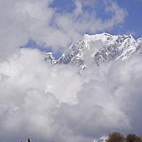 Tibetan villagers rest on a rock below Mt. Namcha Barwa, the highest mountain of eastern Himalaya.(24,440')