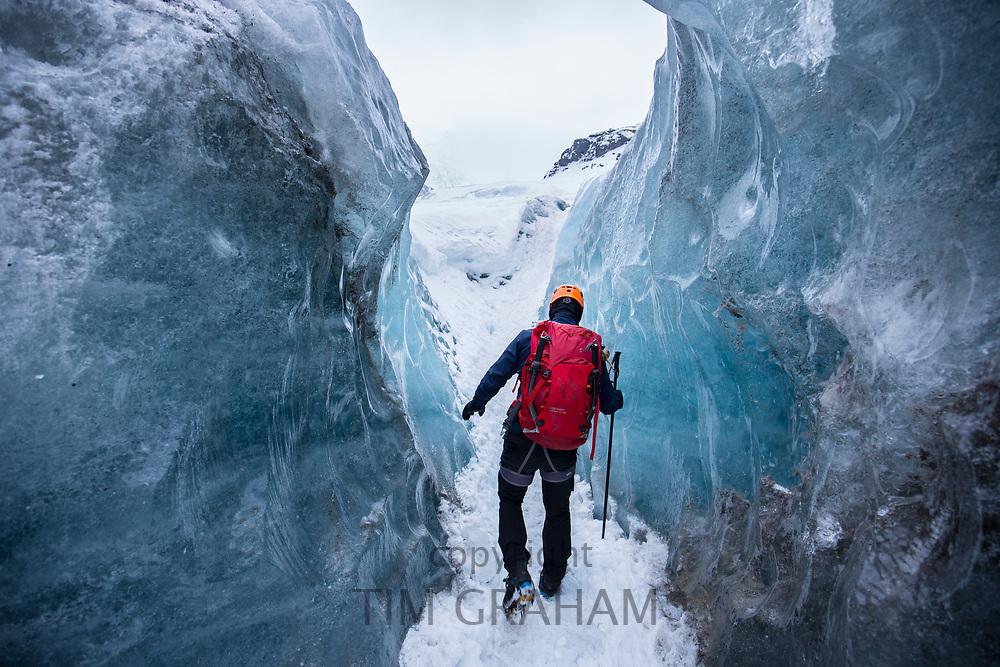 Tourist wearing protective clothing for glacier hike on Svinafellsjokull glacier an outlet glacier of Vatnajokull, South Iceland