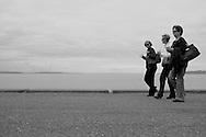 2011 September 14 - Three women walk along the water at Alki Beach, Seattle, WA, USA. Copyright Richard Walker