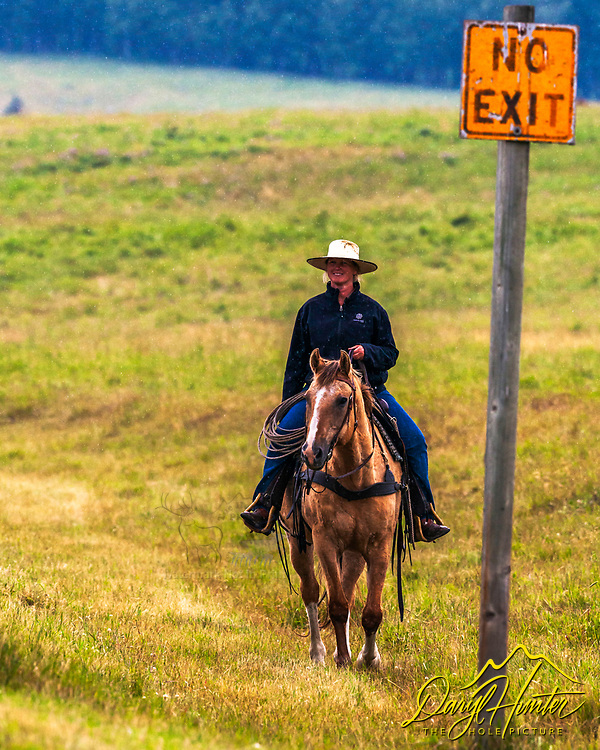 Alberta Rancher Charlotte Esser, happy as a clam in a pouring rain in the Canadian Rockies. Not looking for an exit to the ranching life.