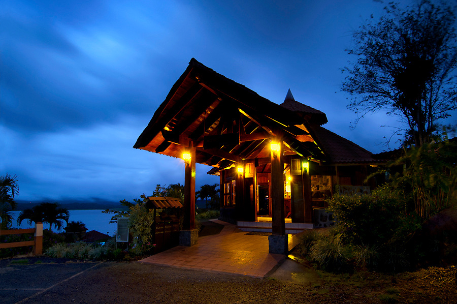 Architecture of a mountain lodge is silhouetted against a blue dusk sky in the Arenal rainforest of Costa Rica