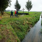 """Nederland Kronenberg 30 september 2008 20080930 Foto: David Rozing ..Serie vernattingscampagne """" Nieuw Limburgs Peil """" de Peel ..Waterschapper Frans van Munnickhof, Bart Tonies en boer Jan van der Sterren inspecteren watergang / stuwtje. Vernattingscampagne """" Nieuw Limburgs Peil """" in omgeving de Peel, uitgevoerd door o.a. de  plaatselijke boeren in samenwerking met het waterschap Peel en Maasvallei. Het doel is een hoger peil van het grondwater dmv het vasthouden van hemelwater. Dit  wordt verwezenlijkt door de aanleg van stuwen in de watergangen bij bv akkers. Door de stuwen in de sloten/ watergangen dicht te zetten wordt het grondwaterpeil hoger in het gebied. Voordelen hiervan zijn: verdroging van de natuur wordt tegen gegaan, voor de boeren kan het drie beregeningen per jaar besparen. Boerenpeil: 400 van de inmiddels 1250 stuwen worden beheerd door de boeren. Natuurgebieden als De Grote Peel en Maria peel hebben veel te lijden gehad onder eerder .waterbeheer:  Het waterschap heeft in het verleden veel akkerslootjes, beken en kanaaltjes aangelegd om ervoor te zorgen dat het water rond dit natuurgebied snel kon wegvloeien, zodat de oogsten.niet zouden verrotten en de akkers goed bewerkbaar waren, maar waardoor nu het waterpeil erg snel zakt..Medewerkers van het waterschap bezoeken de boeren thuis en voeren keukentafelgesprekken met hen om ze te betrekken bij het project. .De Peel is een grotendeels verdwenen hoogveengebied op de grens van de Nederlandse provincies Noord-Brabant en Limburg. ..Foto David Rozing"""
