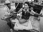 21 FEBRUARY 2014 - KHLONG CHIK, PHRA NAKHON SI AYUTTHAYA, THAILAND:  Thai farmers relax to Thai country music at a roadblock they set up on Highway 32. About 10,000 Thai rice farmers, traveling in nearly 1,000 tractors and farm vehicles, blocked Highway 32 near Bang Pa In in Phra Nakhon Si Ayutthaya province. The farmers were traveling to the airport in Bangkok to protest against the government because they haven't been paid for rice the government bought from them last year. The farmers turned around and went home after they met with government officials who promised to pay the farmers next week. This is the latest blow to the government of Yingluck Shinawatra which is confronting protests led by anti-government groups, legal challenges from the anti-corruption commission and expanding protests from farmers who haven't been paid for rice the government bought.   PHOTO BY JACK KURTZ